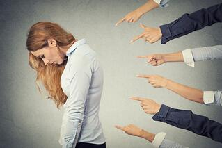 Concept of accusation guilty businesswoman person. Side profile sad upset woman looking down many fingers pointing at her isolated grey office background. Human face expression emotion feeling.jpeg
