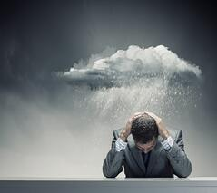 Depressed young businessman sitting wet under rain.jpeg